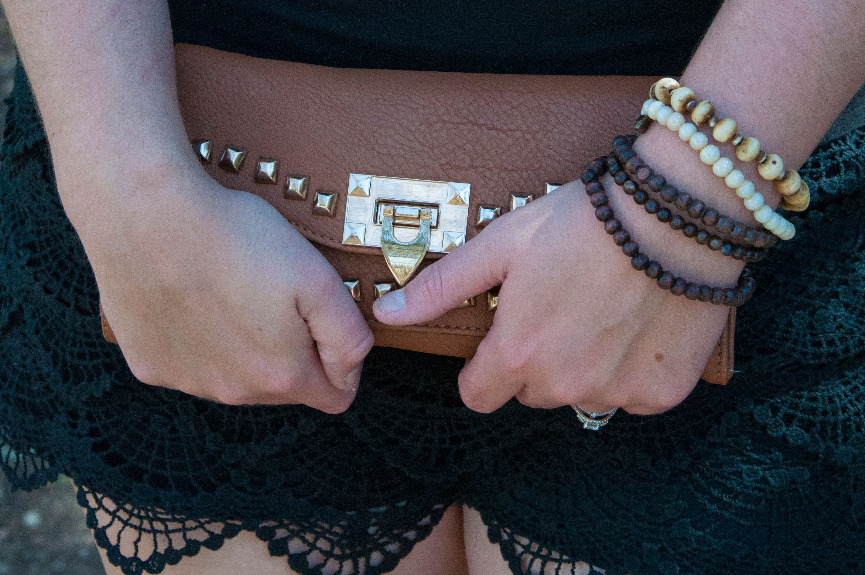 Black lace shorts with cognac clutch