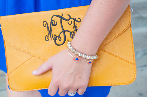 Blue dress with monogram yellow clutch