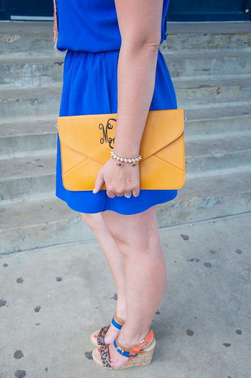 Blue dress with mongrammed yellow clutch