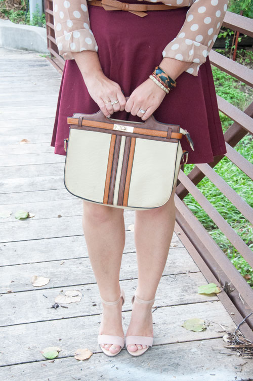 Burgundy skirt and brown striped clutch