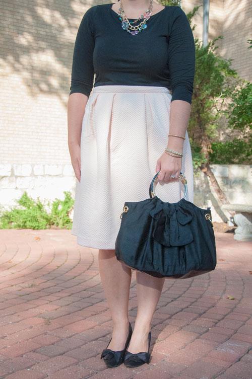 Pale pink midi skirt and black bow handbag
