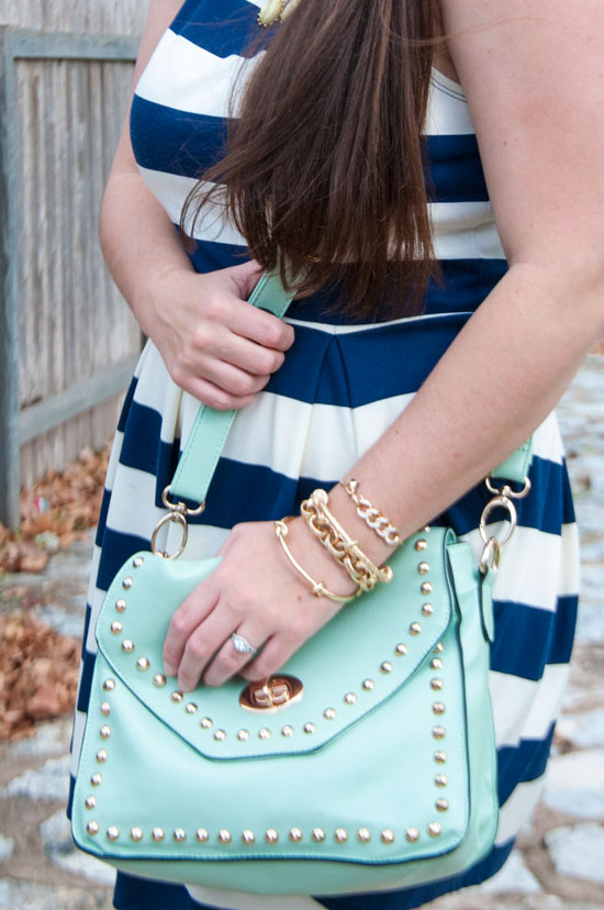 Mint riveted handbag with gold accessories and striped dress